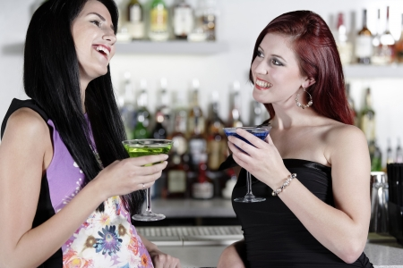 Two beautiful young woman chatting and drinking cocktails at a nightclub or wine bar. Stock Photo - 18000718