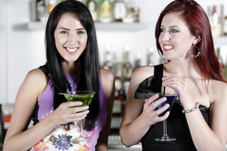 Two beautiful young woman chatting and drinking cocktails at a nightclub or wine bar. photo