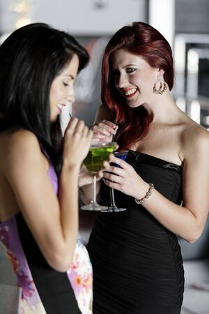 Two beautiful young woman chatting and drinking cocktails at a nightclub or wine bar. Stock Photo - 18000714