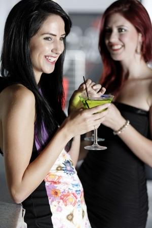 Two beautiful young woman chatting and drinking cocktails at a nightclub or wine bar. Stock Photo - 18000684