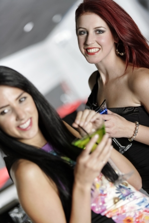 Two beautiful young woman chatting and drinking cocktails at a nightclub or wine bar. Stock Photo - 18000725