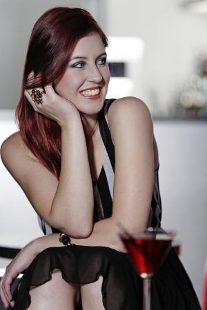 Beautiful young woman sitting in a bar enjoying a drink Stock Photo - 18000712