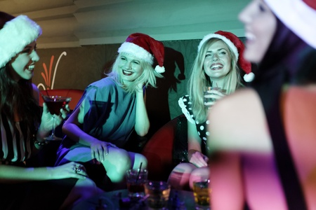 Attractive group of friends laughing and having fun at a Christmas party photo