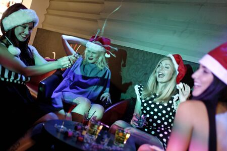 Attractive group of friends laughing and having fun at a Christmas party Stock Photo - 18000692