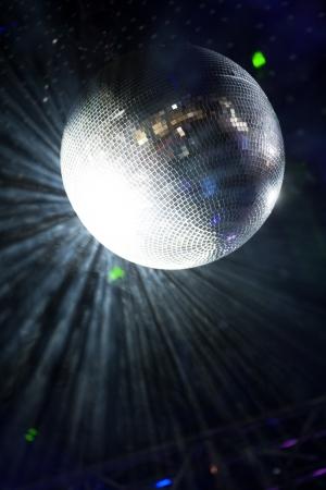 Glitter ball on dance floor with laser lights around