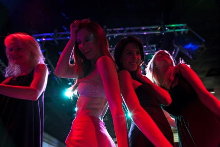 A group of female friends dancing on a nightclub dance floor.