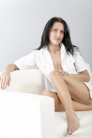 Beautiful young woman sat on a white sofa relaxing. photo