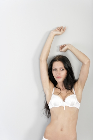 woman bra: Beautiful young woman in white underwear stretching hr arms up relaxing Stock Photo