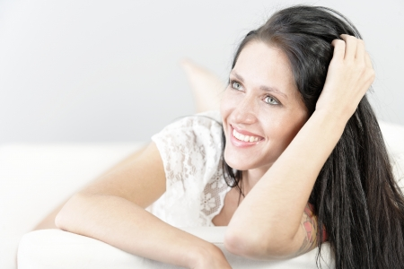 Beautiful young woman with long dark hair lying on her front on a white sofa at home photo