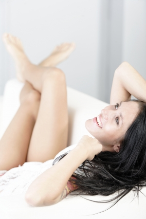 Beautiful young woman with long dark hair lying on her back on a white sofa at home with her legs up photo