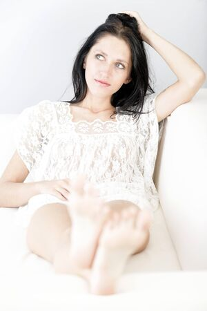foot ware: Beautiful young woman with long dark hair lying on her back on a white sofa at home with her feet up