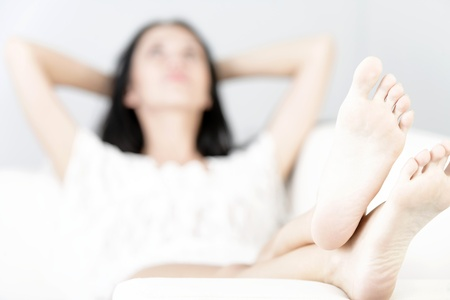 feet relaxing: Beautiful young woman with long dark hair lying on her back on a white sofa at home with her feet up