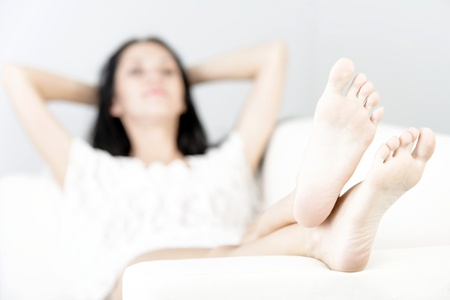 feet up: Beautiful young woman with long dark hair lying on her back on a white sofa at home with her feet up