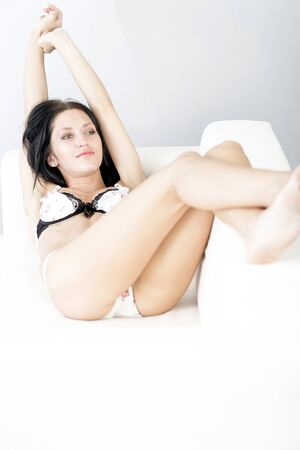 Beautiful young woman lying on a white sofa with her feet up in her underwear. photo