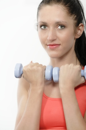 Athletic young woman working out with free weights photo