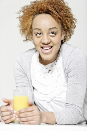 Attractive black woman  relaxing in living room with a glass of juice Stock Photo - 18692702