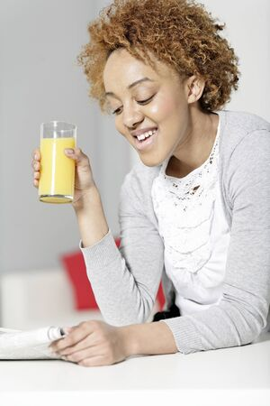Beautiful young black woman reading a newspaper while enjoying fresh juice Stock Photo - 18692714