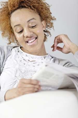 Beautiful young black woman enjoying a newspaper Stock Photo - 18692708
