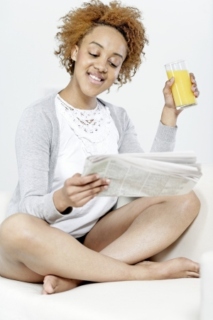 Beautiful young black woman enjoying a newspaper and a glass of juice Stock Photo - 18692704