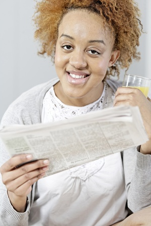 Beautiful young black woman enjoying a newspaper and a glass of juice Stock Photo - 18692711