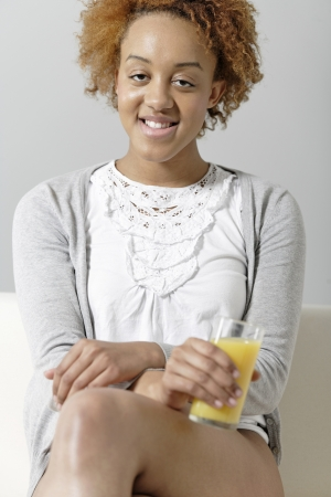 Beautiful young black woman enjoying a glass of fresh juice while sitting on sofa Stock Photo - 18692720