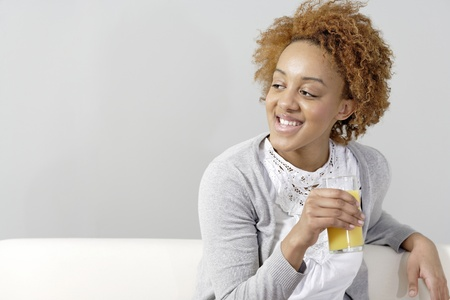 Beautiful young black woman enjoying a glass of fresh juice while sitting on sofa photo