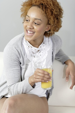 Beautiful young black woman enjoying a glass of fresh juice while sitting on sofa Stock Photo - 18692718
