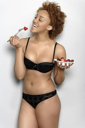 Beautiful young black woman in underwear eating fresh strawberries Stock Photo - 18692726