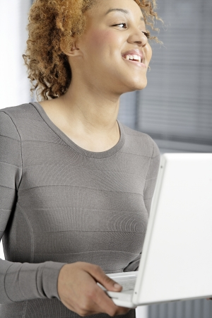 Beautiful young woman holding a laptop computer working Stock Photo - 18692750