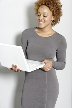 Beautiful young woman holding a laptop computer working Stock Photo - 18692746