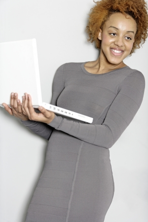 Beautiful young woman holding a laptop computer working Stock Photo - 18692721
