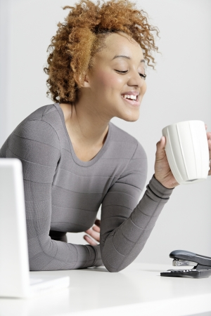 Beautiful young business woman taking a break at her desk Stock Photo - 18692737