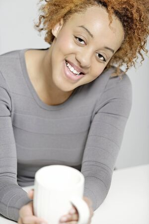 Beautiful young woman enjoying a cup of fresh coffee while having a break Stock Photo - 18692716