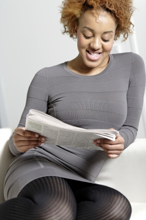 Beautiful young woman reading a newspaper at home Stock Photo - 18692747