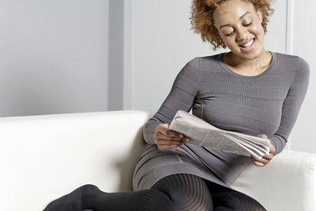 Beautiful young woman reading a newspaper at home Stock Photo - 18692744
