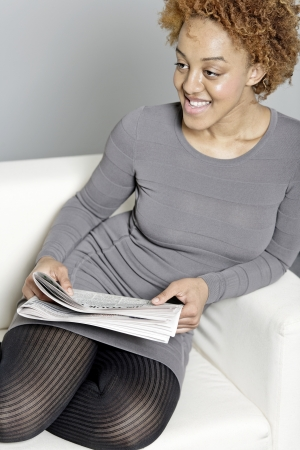 Beautiful young woman reading a newspaper at home Stock Photo - 18692745