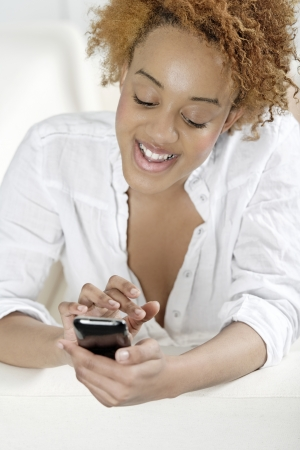 Beautiful young woman texting on her phone to friends Stock Photo - 18692700