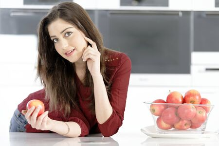 Beautiful young woman eating an apple in her white kitchen photo
