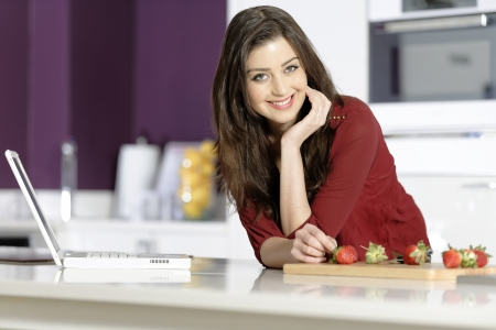 Beautiful young woman reading a recipe from a laptop in her kitchen photo