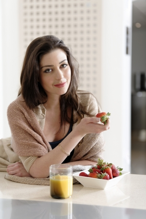 Attractive young woman enjoying a fresh fruit breakfast at home. photo