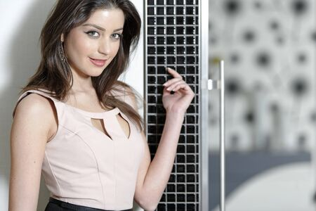 Attractive young woman leaning against a wall in her elegant kitchen. Stock Photo