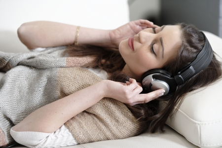 Attractive woman sat on a white sofa listening to music