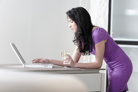 Attractive young woman in a dinner dress using a laptop. photo
