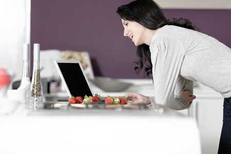 Beautiful young woman reading a recipe from a laptop in her kitchen Stock Photo