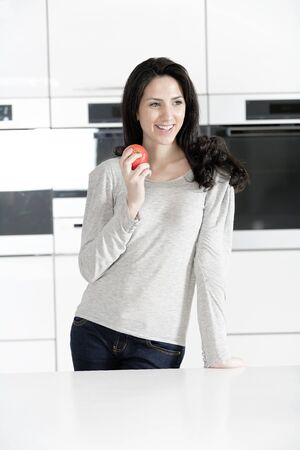 Beautiful young woman eating an apple in her white kitchen relaxing photo