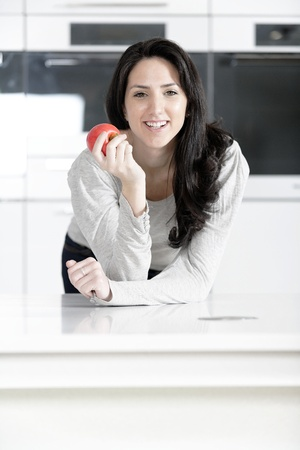 Beautiful young woman eating an apple in her white kitchen relaxing