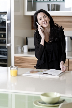 Attractive young woman talking on the phone in her kitchen