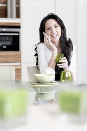 Attractive young woman talking on the phone in her kitchen photo