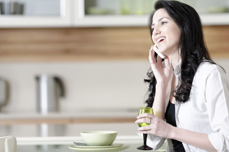 Beautiful young woman chatting on her mobile phone in her kitchen photo