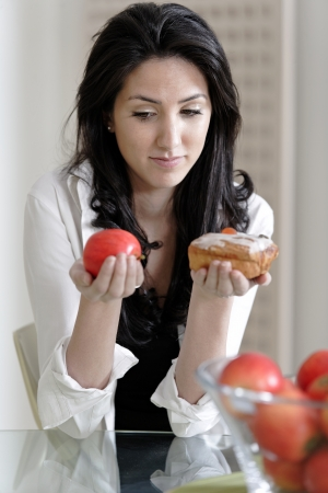 Attractive young woman choosing between a sticky cake or fresh fruit. photo
